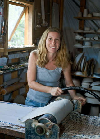 ceramicist: A working potter rolling out clay slabs in her pottery studio.