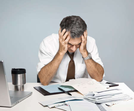 Man paying bills, holding his head, worrying about money and the economy.