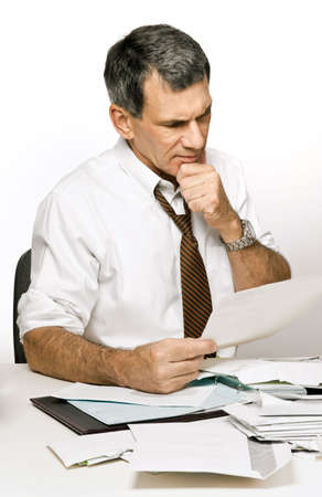 Businessman at desk in shirt and tie, reading a bill and looking worried and confused.