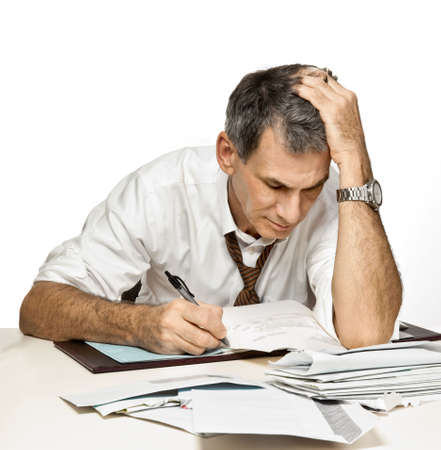 Man at desk in shirt and tie paying bills, writing checks and feeling frustrated and worried.
