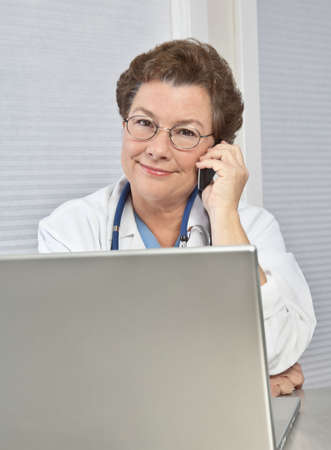 A female medical doctor at her laptop, talking on the phone. photo