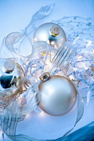 An abstract tangle of glowing silvery Christmas ornaments with translucent ribbons, sparkling gold stars and twinkling white lights. Short depth of field with glowing effects and toned blue.  photo