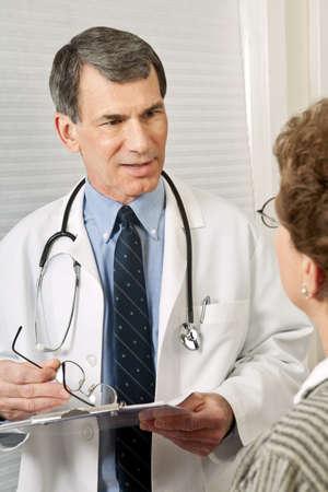 Médecin homme parler avec un patient femelle pendant un bureau visiter.  Banque d'images - 6022252