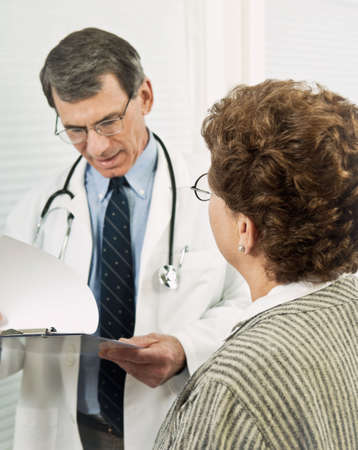Male doctor talking with female patient. Patient is in sharp focus in the foreground with doctor blurred with background. Stock Photo