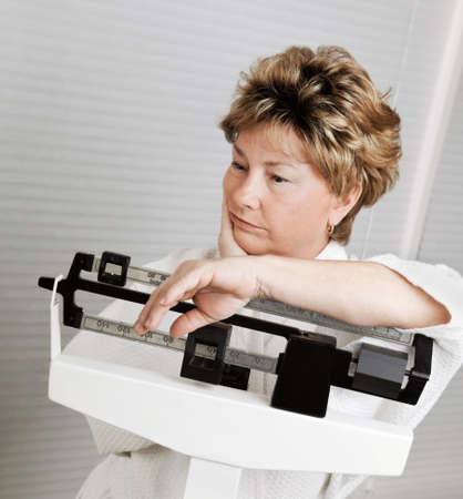 menopause: Mature woman looks disappointed at her progress losing weight, on weight scale.