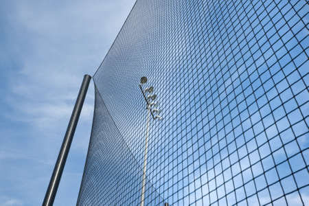 Dramatic wide angle view of backstop net and stadium lights at baseball or softball playing field. Angle is looking up towards the sky on a sunny day with blue sky and white clouds.  photo