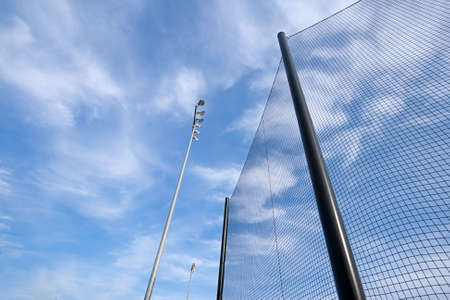 Wide angle view of backstop net and stadium lights at baseball or softball playing field. Angle is looking up towards the sky on a sunny day with blue sky and white clouds. Good abstract shot or background.