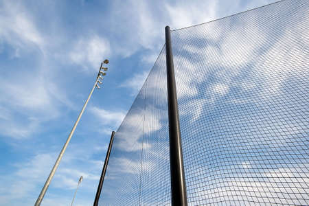 backstop: Extreme wide angle view of backstop net and stadium lights at baseball or softball playing field. Angle is looking up towards the sky on a sunny day. Stock Photo
