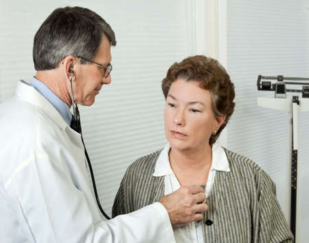 Male doctor listens to mature womans heart during an office visit.