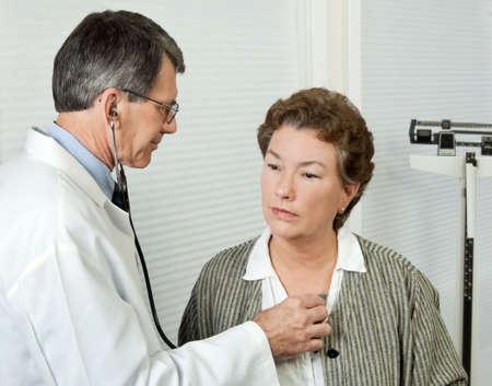 male doctor: Medico maschio � in attesa di maturare il cuore della donna durante una visita di ufficio. Archivio Fotografico