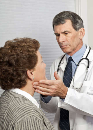 Doctor examining mature female patient for flu symptoms in office photo