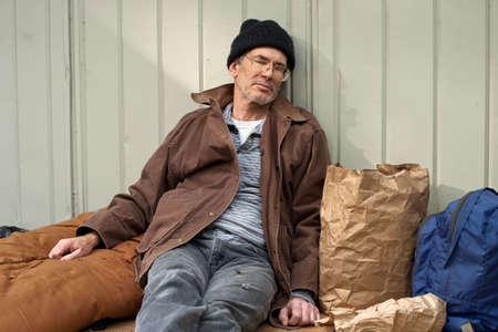 Volwassen dakloze man slapen in een zittende houding, leunend op een metalen wand, omringd door zijn pack, slaap zak, enzovoort.  Stockfoto