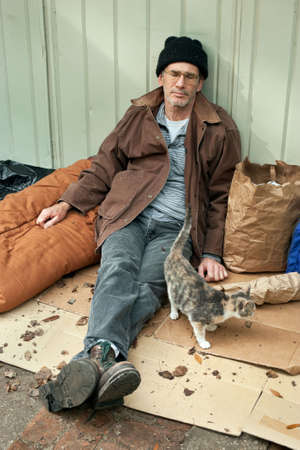 wino: Resigned looking mature homeless man seated on the street with watching a friendly stray cat.