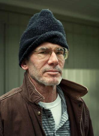 Close-up milieu portret van een oudere dakloze man op zoek recht op de camera, op zoek ernstige.