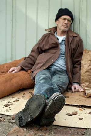 Homeless man sleeping on the streets, seated position, surrounded by his bags, etc. Selective focus with boot soles full of holes in focus, and the mans face blurry.