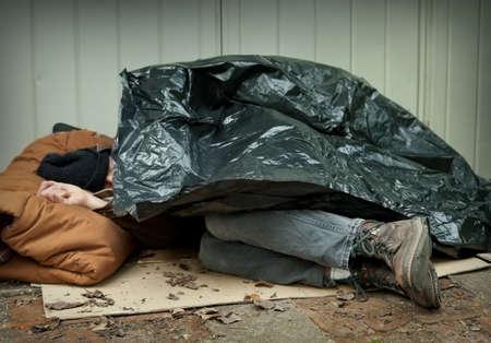 ホームレスの男性が路上で眠っている、プラスチック防水シートの下に丸まって