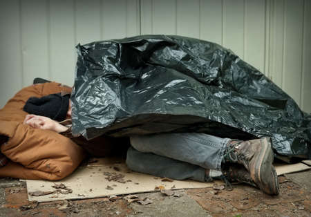 Homeless man curled up under a plastic tarpaulin, asleep on the street  Stockfoto
