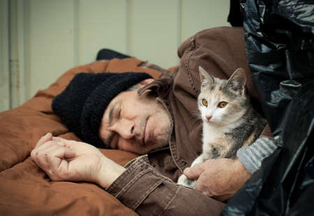calico: Closeup portrait of a homeless older man sleeping under a plastic tarp on the street with a friendly stray kitten. Selective focus on the mans hands and the kitten. Stock Photo