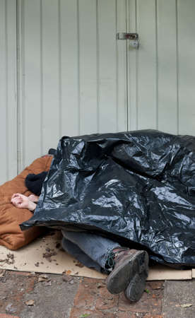 Passed out: Homeless man curled up asleep under a plastic tarp on the street