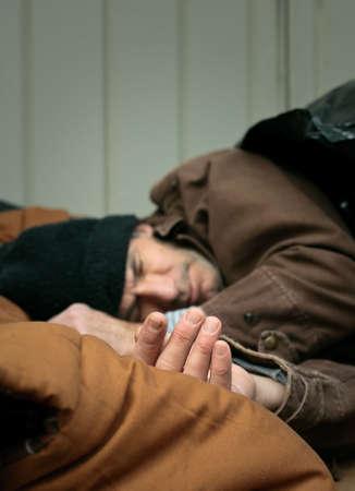 hombre pobre: Profundidad corto de campo portarretrato disparo del hombre sin hogar durmiendo en la calle. Mano est� en foco... resto gradualmente est� borrosa.