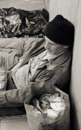 Sepia toned of a homeless man on the street, seated, surrounded by his meager belongings. photo
