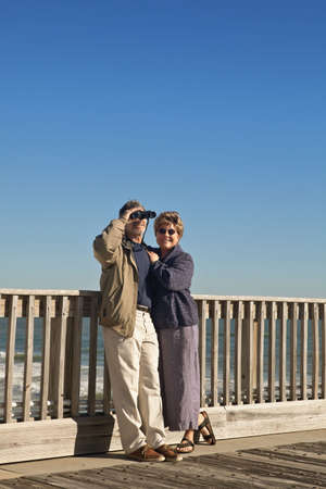 Happy mature, senior couple on a wooden seaside pier with the ocean in the background. Stock Photo - 6292102