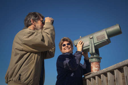 Happy retired couple on a beach boardwalk, skywatching and birdwatching with binoculars and telescope  photo