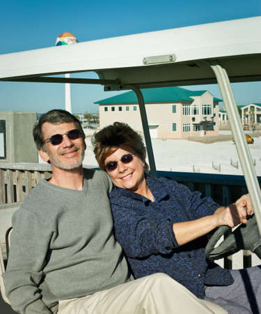 Happy retired couple having fun in an old golf cart at the beach. photo