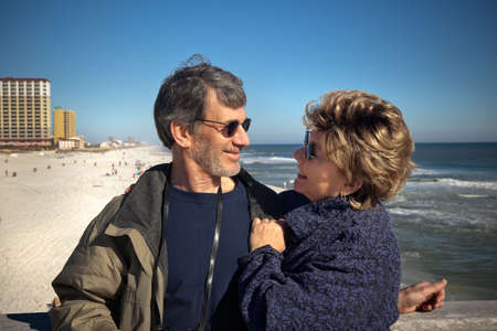 Happy senior couple enjoying themselves at a beautiful beach on their winter or spring vacation. Wide view of Couple gazing affectionate at each other with the beach and ocean and hotels in the background.