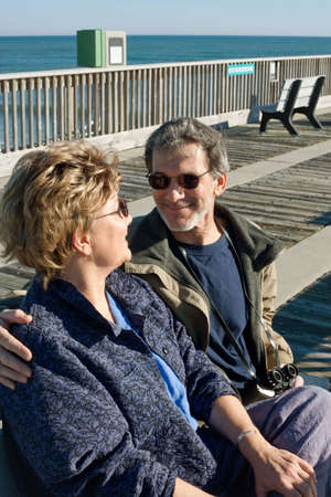 Happy mature couple seated on a park bench on the boardwalk at the ocean  photo