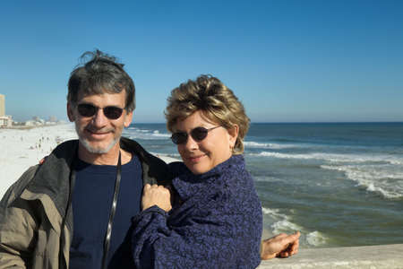 Happy senior couple cuddling at the beach on winter vacation. photo