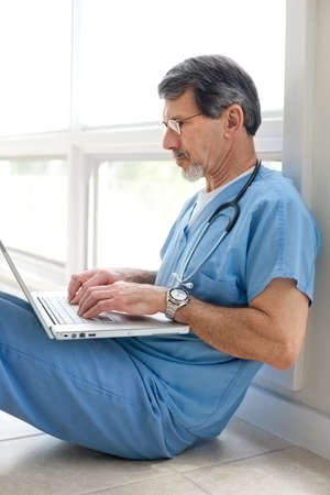 Mature doctor sitting on floor reviewing data on his laptop computer. Light and bright exposure. photo