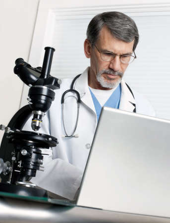 A doctor researching at the microscope and laptop computer. photo