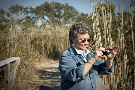 Mature woman having fun with her small digital camera on vacation, hiking and birdwatching in a national park. photo
