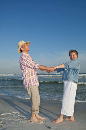 Happy mature couple dancing and horsing around on the beach at sunset.