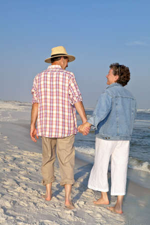 Happy mature couple strolling hand in hand on the beach at sunset. Main focus on the woman. photo