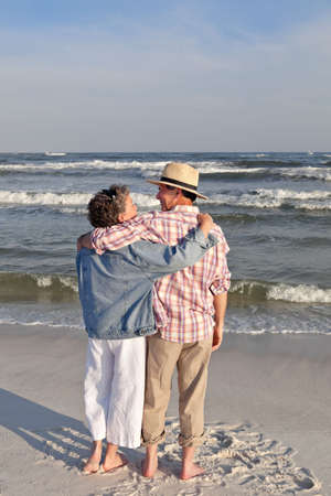 Affection mature couple standing at the water's edge at the beach in the rosy light of sunset.