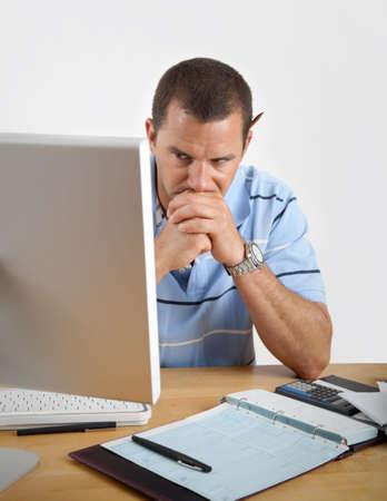 젊은 남자가 컴퓨터, 수 표 및 계산기 그의 책상에 앉아 피곤, 좌절 하 고 걱정으로 찾고.