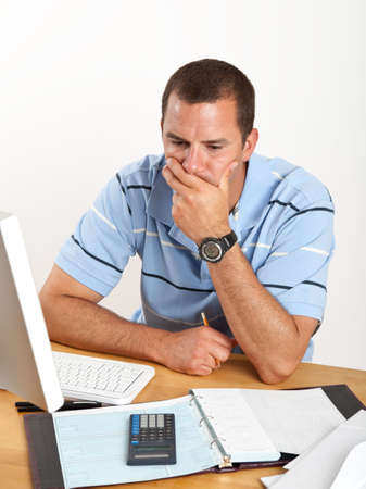 checkbook: Joven preocupado, estresado sobre proyectos de ley y las finanzas, sentado en el escritorio con chequera y equipo.  Foto de archivo