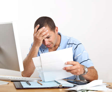 Young man at desk with computer and checkbook, worrying about paying bills, holding his head.