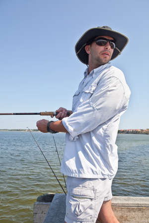 sunhat: Handsome man with sunglasses and sunhat fishing from a pier on a sunny day.