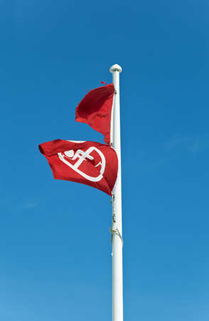 flagpole: Two red flags on a flagpole at a Gulf Coast Beach mean no swimming or fishing due to dangerous surf, storms, or in this case, toxicity from an oil spill