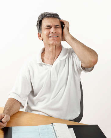 worrying: Mature man with headache holding head and worrying about the economy and retirement.