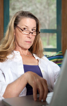 Pretty, serious woman with glasses at laptop computer looking directly at camera. photo