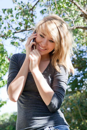 phone: Pretty blond teenage girl talking on cell phone (mobile phone) outdoors on a sunny day.