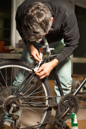 Man Repairing and Rebuilding An Old Bicycle Stock Photo - 9386250