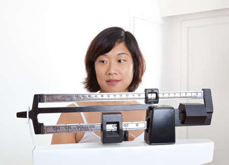 Pretty woman closeup measuring her weight loss or gain on a physicians weight scale. photo