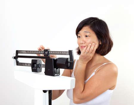 gewicht skala: H�bsch Mittelalter Frau auf vertikale Waage suchen entt�uscht �ber ihr aktuelles Gewicht