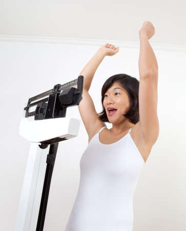 Cute, mature woman on a weight scale cheering happily at reaching her target weight. White background, closeup photo