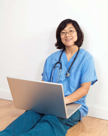 smiing: Smiing woman nurse or doctor, seated on floor with laptop computer Stock Photo